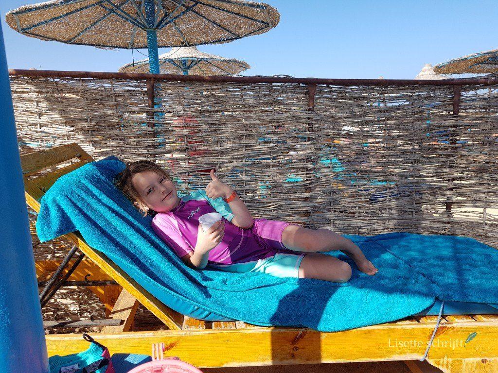 Meisje op ligbed op het strand in Egypte Lisette Schrijft