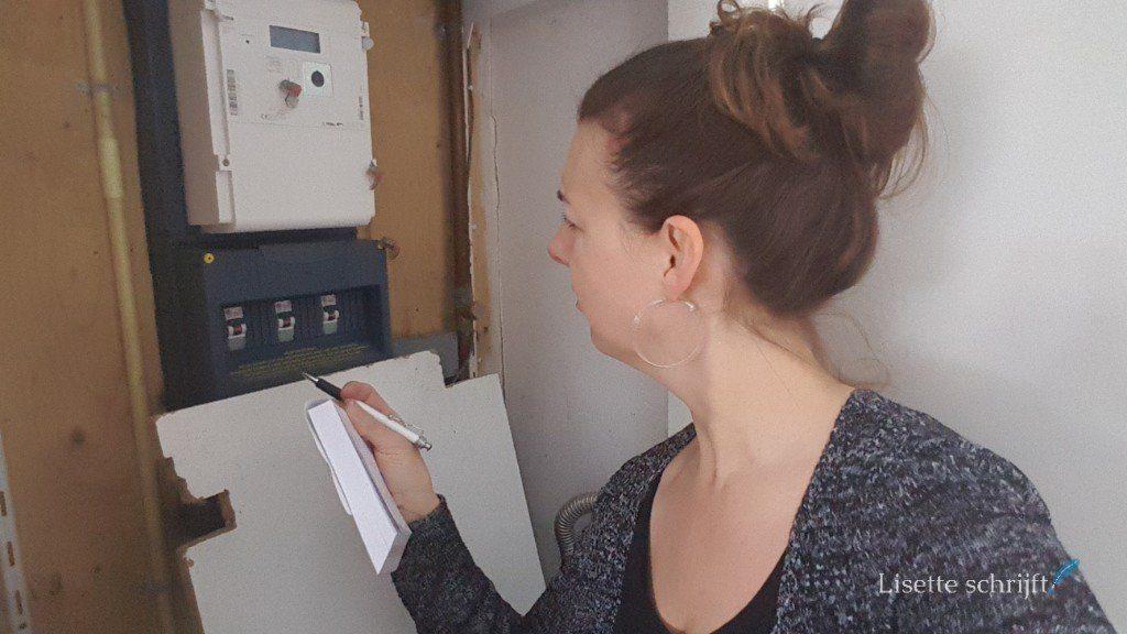 vrouw zoekt de meterstanden op in de meterkast