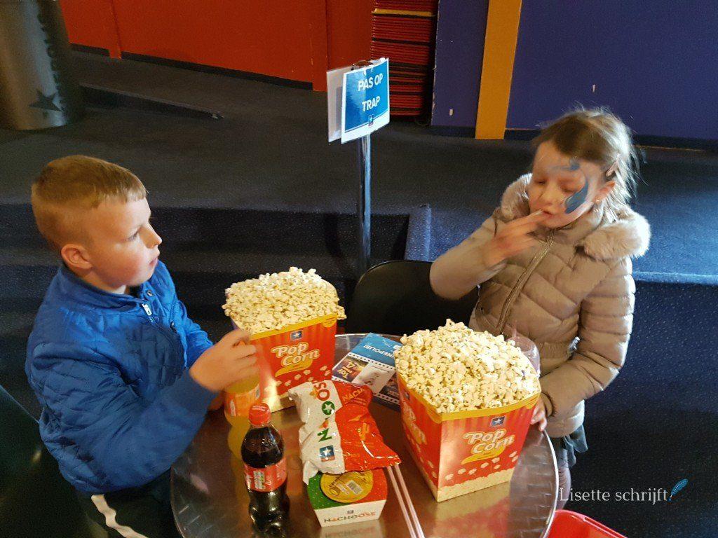 2 kinderen met grote bakken popcorn