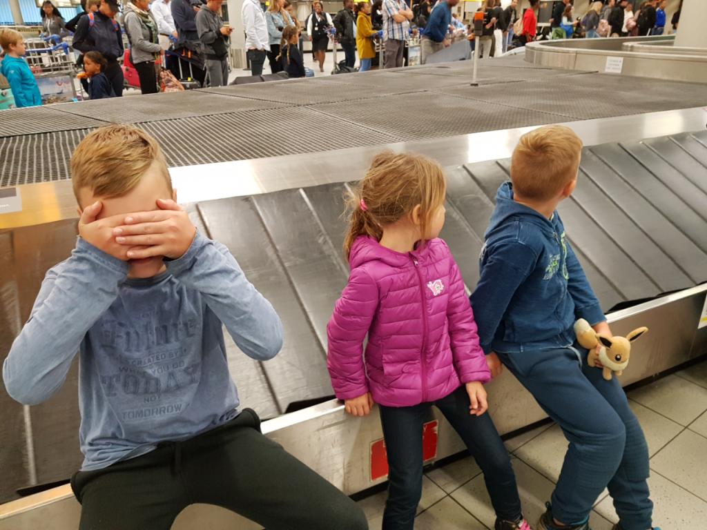 kinderen bij de kofferband op schiphol